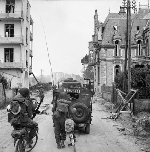A_jeep_and_other_vehicles_and_troops_passing_through_La_Breche_as_they_move_inland_from_Sword_Beach,_Normandy,_6_June_1944._B5036