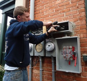 Electrician_installing_outdoor_connections_on_multifamily_house