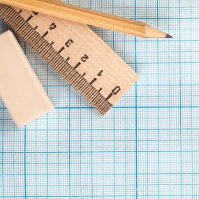 Maths equiptment on graph paper including a pencil, rubber and a ruler