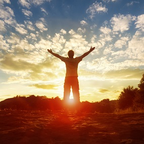 person with arms outstretched and sun setting in the bankground